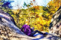 Teenage Girl Sitting on Rocks at Kent Falls. A blond hair girl with braids sitting on a large rocks at Kent Falls State Park in Kent Connecticut in autumn stock photo