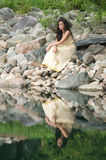 Teenage girl sitting on rocks by pond Royalty Free Stock Photography