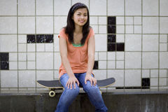 Teenage girl (13-15) sitting on skateboard, smiling, portrait Royalty Free Stock Photos