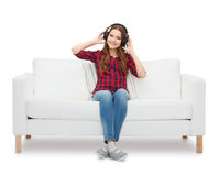 Teenage girl sitting on sofa with headphones Royalty Free Stock Photography