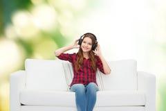 Teenage girl sitting on sofa with headphones Stock Photography