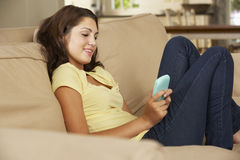Teenage Girl Sitting On Sofa At Home Texting On Mobile Phone Royalty Free Stock Photography