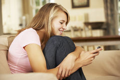 Teenage Girl Sitting On Sofa At Home Texting On Mobile Phone Stock Image