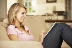 Teenage Girl Sitting On Sofa At Home Using Tablet Computer Stock Photos
