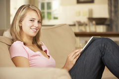 Teenage Girl Sitting On Sofa At Home Using Tablet Computer Royalty Free Stock Photos