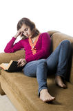 Teenage girl sitting on sofa reading Royalty Free Stock Image