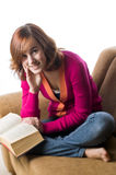 Teenage girl sitting on sofa reading a book Royalty Free Stock Images