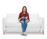 Teenage girl sitting on sofa with tablet pc Stock Photo