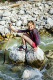 Teenage girl sitting on stone. Small mountains river Royalty Free Stock Photo