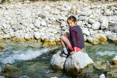 Teenage girl sitting on stone. Small mountains river Stock Photo