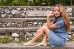 A teenage girl is sitting on stone steps outdoors. Walking. Stock Photo