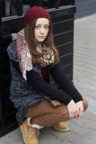 A teenage girl is sitting on the street Royalty Free Stock Photo