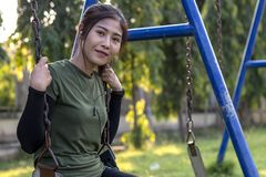 Teenage girl sitting on a swing chain smiling. Close-up of a young woman wearing a green t-shirt sitting happily hanging with a chain of swings in a park royalty free stock photos