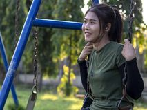 Teenage girl sitting on a swing chain smiling. Close-up of a young woman wearing a green t-shirt sitting happily hanging with a chain of swings in a park royalty free stock image