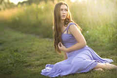 A teenage girl sitting in tall grasses in the summer. Stock Photo