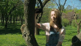 A teenage girl is sitting on a tree with a phone. A girl in ripped jeans makes selfie. Beautiful girl in the park. stock video