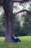 Teenage girl sitting under the tree and reading book Stock Images