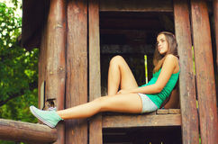 Teenage girl sitting in the wooden house Stock Photography