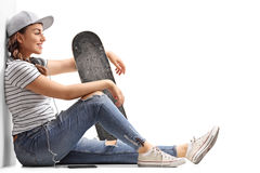 Teenage girl with a skateboard leaning against a wall Stock Photos