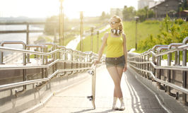 Teenage girl with skateboard Stock Images