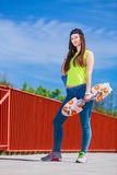 Teenage girl skater riding skateboard on street. Royalty Free Stock Photography