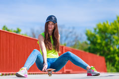 Teenage girl skater riding skateboard on street. Royalty Free Stock Photo