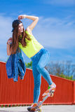 Teenage girl skater riding skateboard on street. Royalty Free Stock Images