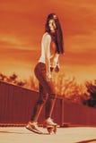 Teenage girl skater riding skateboard on street. Stock Images