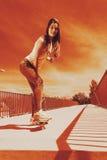 Teenage girl skater riding skateboard on street. Royalty Free Stock Photography