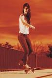 Teenage girl skater riding skateboard on street. Stock Photos