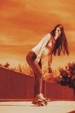 Teenage girl skater riding skateboard on street. Stock Photography