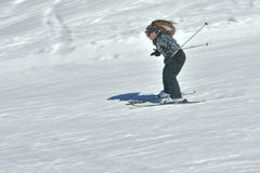 Teenage girl skiing in Austria. Skiiing fast  on a sunny spring day in the Lech - Zurs Arlberg ski resort in the Tyrol, Austria.  Blurred motion showing speed Royalty Free Stock Photo
