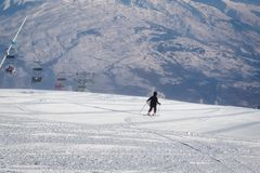 Teenage girl skiing downhill on the freshly groomed ski slope. View of the valley in French Alps in background stock photos