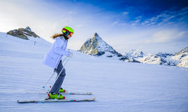 Teenage girl skiing in Swiss Alps. Teenage girl skiing in Swiss Alps in Sunny Day, Matterhorn in Background Stock Photo