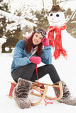 Teenage Girl With Sledge Next To Snowman Royalty Free Stock Photography