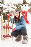 Teenage Girl With Sledge Next To Snowman Royalty Free Stock Photos