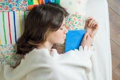 Teenage girl is sleeping in bed, holding book in her hands.  Stock Photos