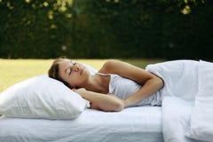 Girl sleeping on matress on grass stock photography