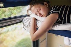 Teenage girl sleeps in train Stock Photo