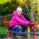 Teenage girl on small roundabout Stock Photo
