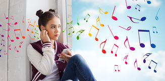 Teenage girl with smartphone and earphones. People, technology and teens concept - sad pretty teenage girl sitting on windowsill with smartphone and earphones Royalty Free Stock Photos