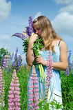 Teenage girl smelling lupine flowers Royalty Free Stock Image
