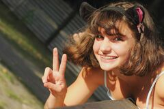 Teenage girl smiles positively and shows victory sign. Positive smile concept under different circumstances