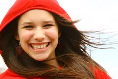 Teenage girl smiling. A young teenage girl smiling wearing a red hoodie Stock Image