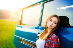 Teenage girl smiling against green campervan outside in nature Stock Image