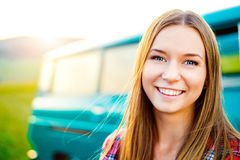 Teenage girl smiling against green campervan outside in nature Royalty Free Stock Photo