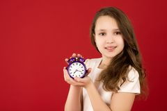 Teenage girl smiling with alarm clock in hands on red royalty free stock images