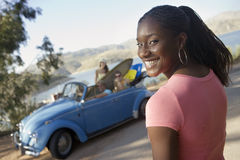Teenage girl (17-19) smiling, friends in car with surfboard, portrait, focus on foreground (tilt) Stock Image