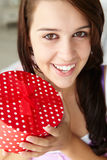 Teenage girl smiling and holding red gift box Stock Image