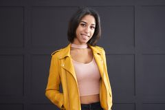 Teenage girl smiling in yellow leather jacket stock photo